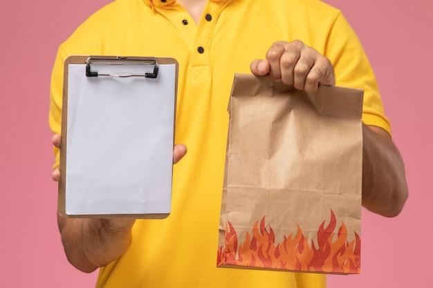 Спереди крупным планом мужской курьер в желтой форме держит блокнот и пакет с едой на розовом столе Бесплатные Фотографии