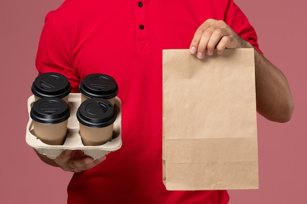 Front close view male courier in red uniform holding brown delivery coffee cups with food package on the pink wall service delivery job worker uniform Free Photo