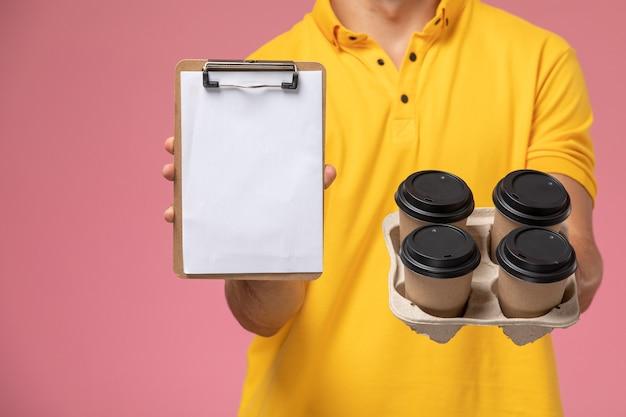 Corriere maschio di vista ravvicinata anteriore in blocco note giallo della tenuta uniforme e tazze di caffè di consegna sullo scrittorio rosa Foto Gratuite
