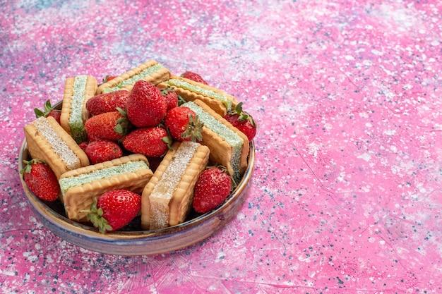 ピンクの壁に新鮮な赤いイチゴとおいしいワッフルクッキーの正面の拡大図 無料写真