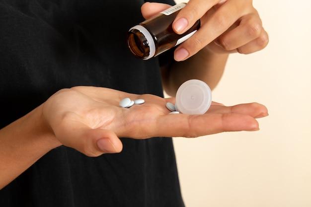 Donna giovane malata vista ravvicinata anteriore che si sente molto male e che prende le pillole sulla superficie bianca Foto Gratuite