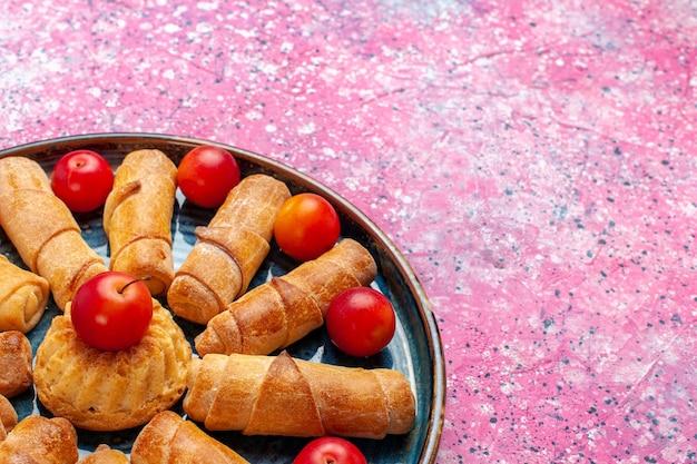 ピンクの机の上に梅とトレイの中に甘いおいしいベーグル焼きペストリーを正面から見る 無料写真