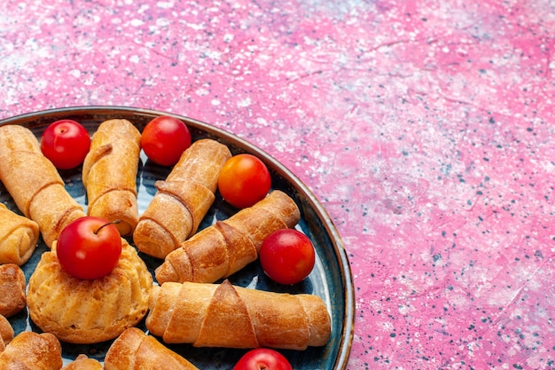 Front close view sweet delicious bagels baked pastries inside tray with plums on pink desk Free Photo