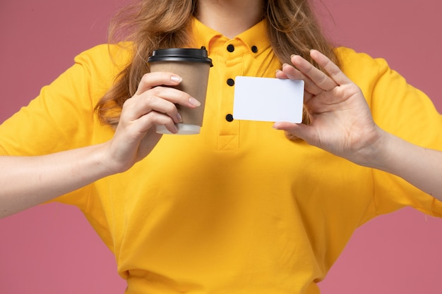 Вид спереди крупным планом молодая женщина-курьер в желтой форме, держащая чашку кофе и белую карточку на розовом фоне, рабочий стол службы доставки униформы Бесплатные Фотографии