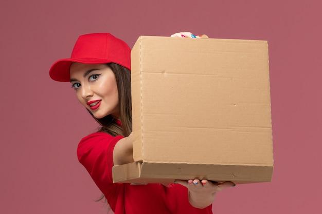 Corriere femmina giovane vista ravvicinata anteriore in scatola di cibo consegna azienda uniforme rossa su sfondo rosa chiaro azienda uniforme di lavoro di consegna servizio Foto Gratuite
