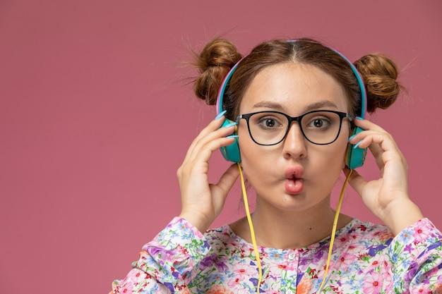 Vista ravvicinata anteriore giovane femmina in fiore progettato camicia e blue jeans ascoltando musica con gli auricolari sullo sfondo rosa Foto Gratuite