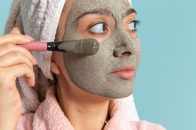 Giovane femmina di vista ravvicinata anteriore in accappatoio rosa dopo la doccia che applica la maschera sulla superficie blu Foto Gratuite