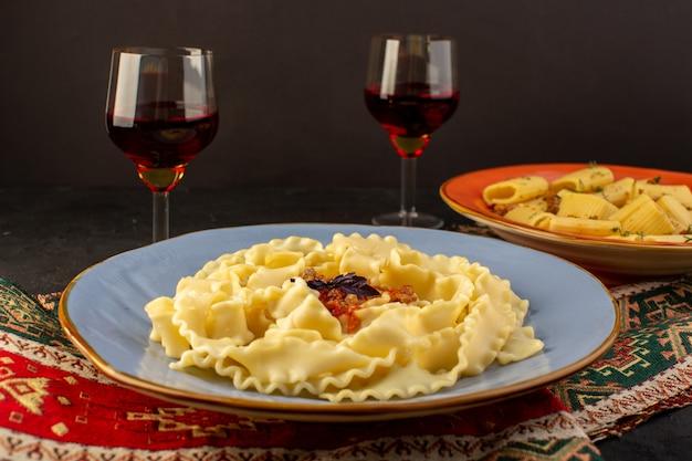 Una pasta di pasta vista frontale chiusa cucinata gustosa salata all'interno di un piatto rotondo blu con bicchieri di vino sul tappeto progettato e scrivania scura Foto Gratuite