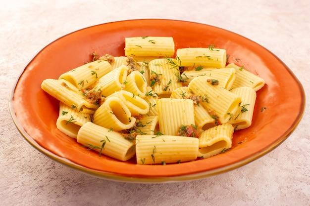 Una pasta italiana di vista frontale chiusa cucinata gustosa con verdure secche e salata all'interno del piatto arancione rotondo sullo scrittorio rosa Foto Gratuite