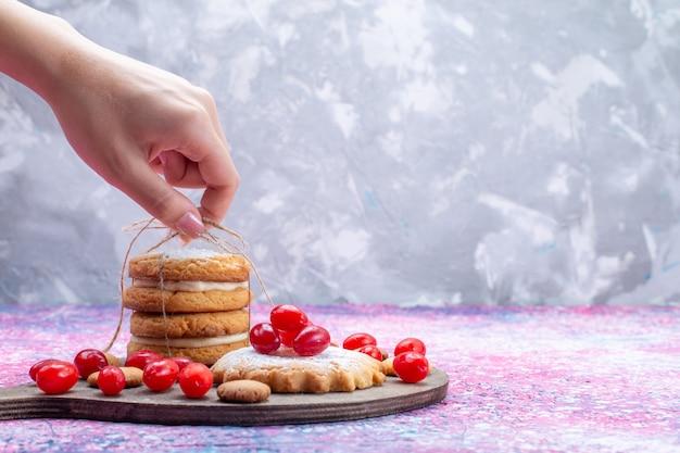 Сливочное печенье-сэндвич с красным кизилом, принимающее женщину на ярком Бесплатные Фотографии