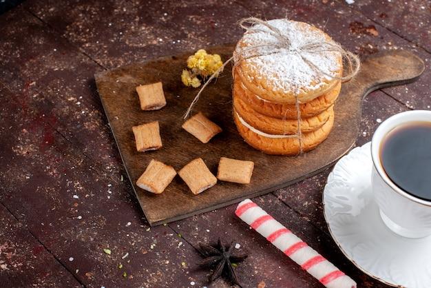Вид спереди ближе чашка кофе крепкого и горячего вместе с печеньем и сэндвич-печеньями на деревянном коричневом Бесплатные Фотографии