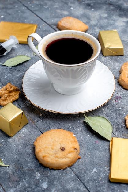 Вид спереди ближе чашка кофе с печеньем грецкими орехами на сером печенье, бисквите, сладкой выпечке Бесплатные Фотографии