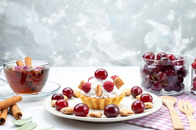 Вид спереди ближе маленький кремовый торт с малиной, вишней и маленьким печеньем, чай с корицей на светлом столе Бесплатные Фотографии