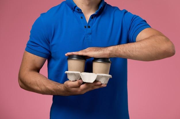 Спереди ближе вид мужчина-курьер в синей форме, держащий кофейные чашки на розовом, униформе работника службы доставки Бесплатные Фотографии