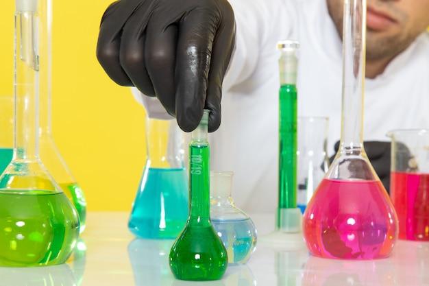 Передний близкий вид молодого мужчины-химика в белом костюме перед столом с цветными растворами, держащего колбу на желтом столе, в научной лаборатории Бесплатные Фотографии