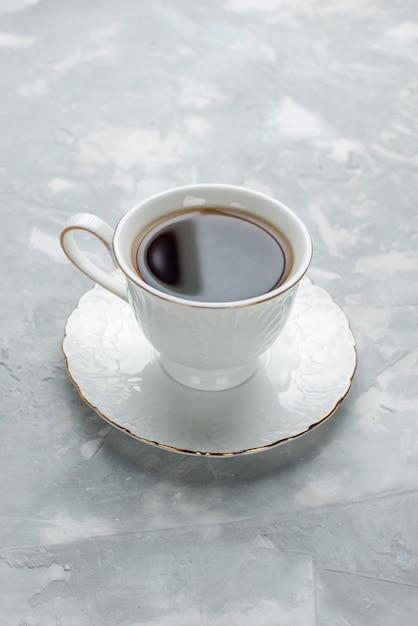 ライトデスクのガラスプレート上の白いカップの中に熱いお茶の正面の遠景カップ 無料写真