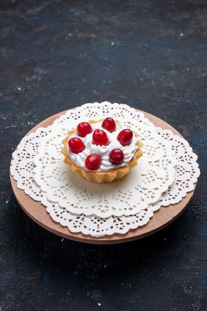 Спереди вдалеке вкусный торт со сливками и красными фруктами на темной поверхности торта фруктов Бесплатные Фотографии