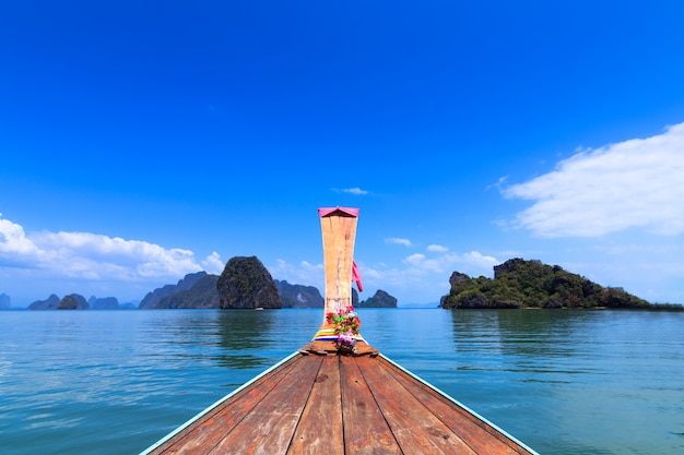 A front of long tail boat and view of phuket sea at thailand . adaman sea and wooden boat Premium Photo
