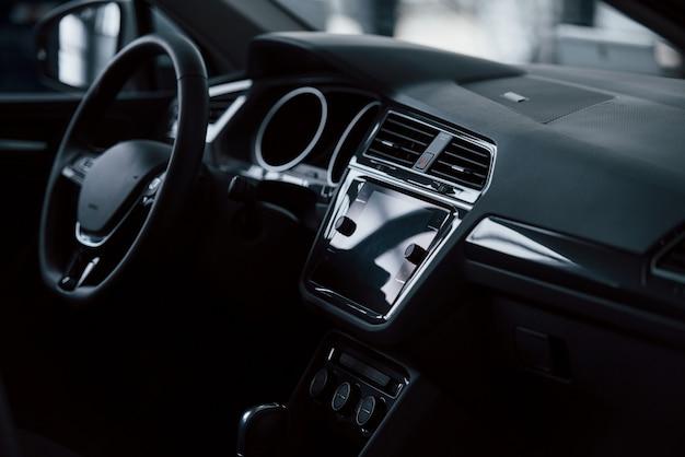 Parte anteriore dell'automobile nuova di zecca. interni neri moderni. concezione dei veicoli Foto Gratuite