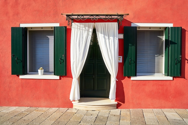 Front of the red house on the island of burano. italy, venice Premium Photo