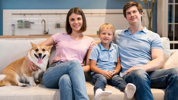 正面の愛らしい家族が犬と一緒にポーズ Premium写真