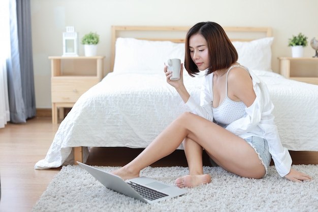 Front view of adult freelance asian woman in white shirt working on computer while drinking coffee or tea in bedroom Premium Photo