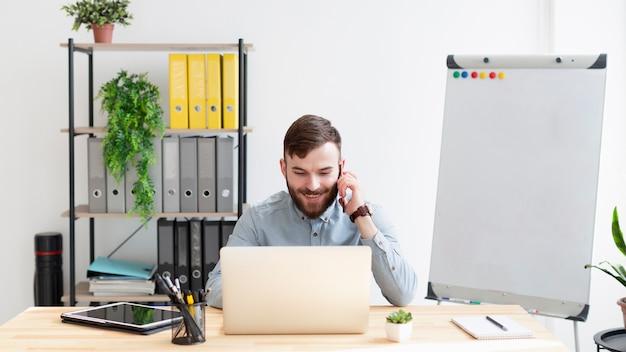オフィスで仕事を楽しんでいる正面成人男性 Premium写真