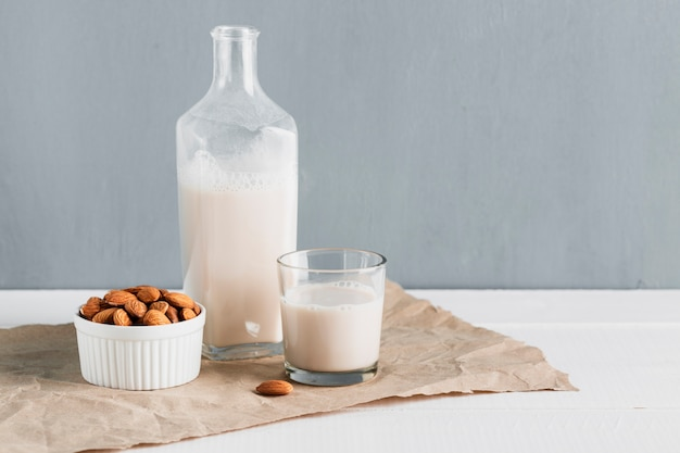 Front view almonds with glass and bottle of milk Free Photo