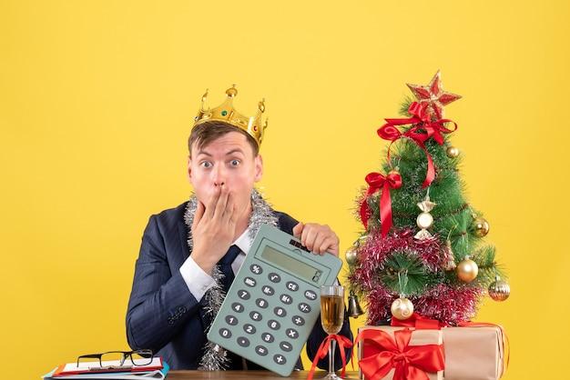 Vista frontale dell'uomo stupito che tiene la calcolatrice che si siede al tavolo vicino all'albero di natale e presenta sulla parete gialla Foto Gratuite