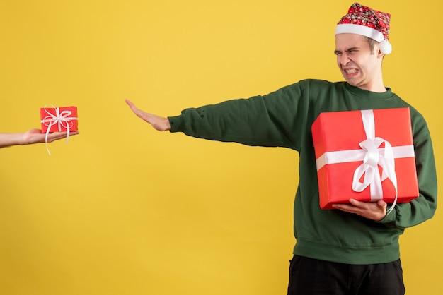 Vista frontale uomo arrabbiato chiudendo gli occhi rifiutando il dono in mano femminile su colore giallo Foto Gratuite