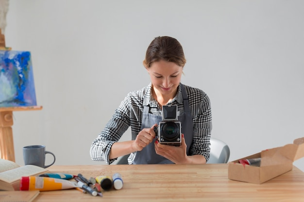Front view of artist in apron holding retro camera Free Photo