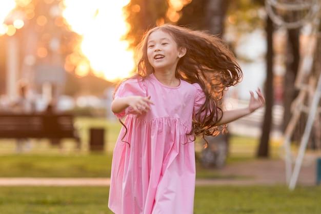 Bambina asiatica di vista frontale con capelli lunghi che funzionano nel parco Foto Gratuite