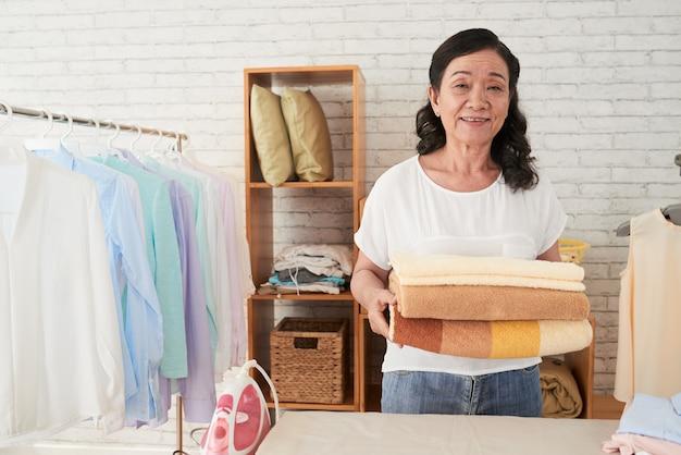 Vista frontale di asianhousemaid che sta con gli asciugamani nella stanza di lavanderia Foto Gratuite