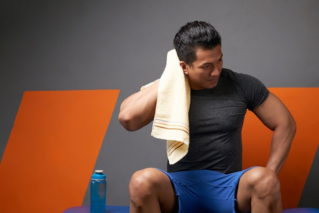Front view of athletic man wiping his head with towel relaxing after the workout Free Photo