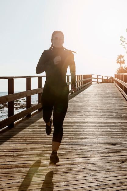 Vista frontale della donna atletica che pareggia sulla spiaggia con lo spazio della copia Foto Gratuite