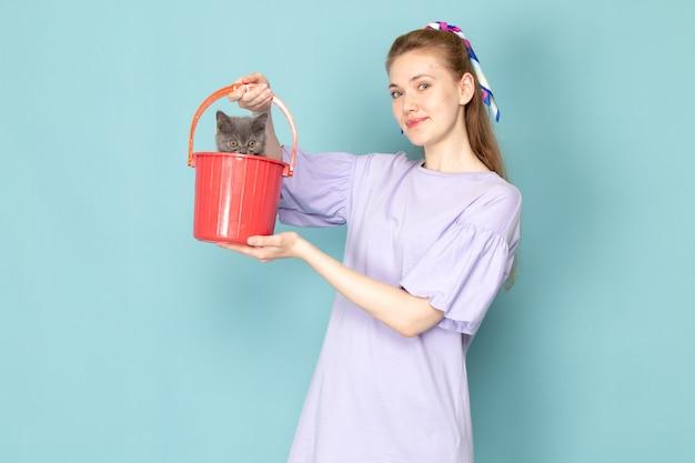 Una femmina attraente di vista frontale in camicia viola che tiene secchio rosso con il gattino sveglio sull'azzurro Foto Gratuite