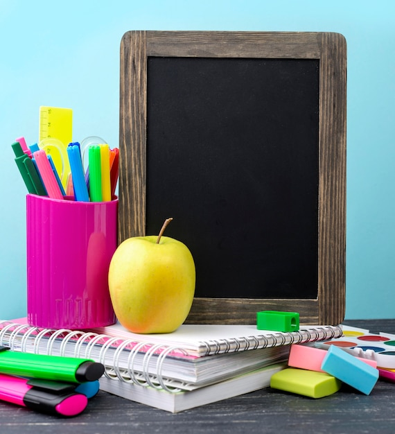 Front view of back to school stationery with pencils and apple Free Photo