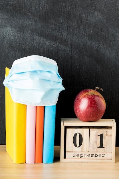 Vista frontale del ritorno a materiale scolastico con maschera medica e libri Foto Gratuite