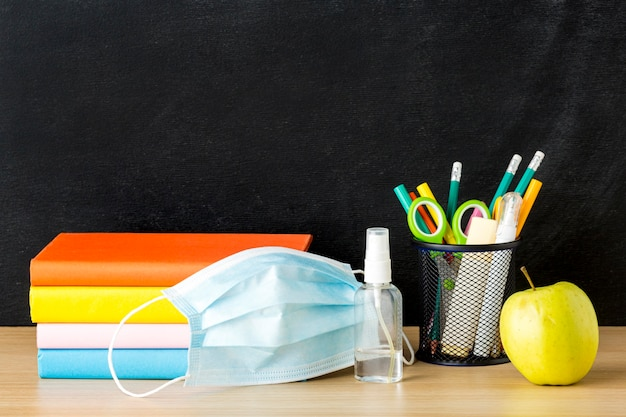 Front view of back to school supplies with medical mask and books Free Photo
