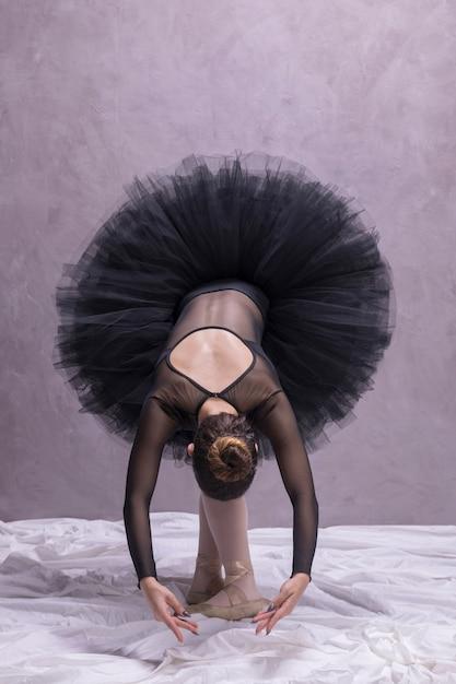 Front view ballerina bending pose Free Photo