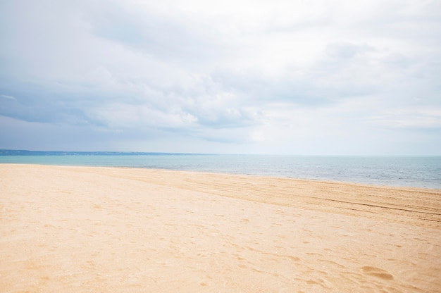 Front view of beach with sand and clouds Free Photo