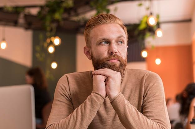 Vista frontale uomo barbuto che guarda lontano Foto Gratuite