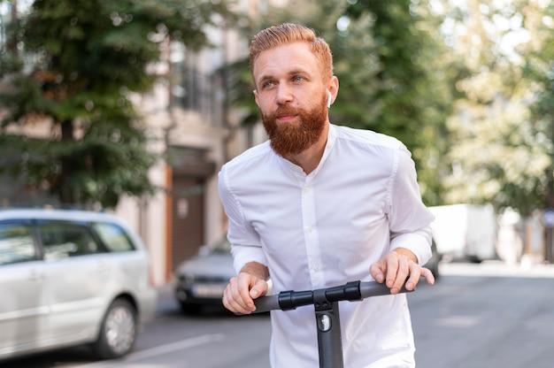 Vista frontale barbuto uomo moderno su scooter all'esterno Foto Gratuite