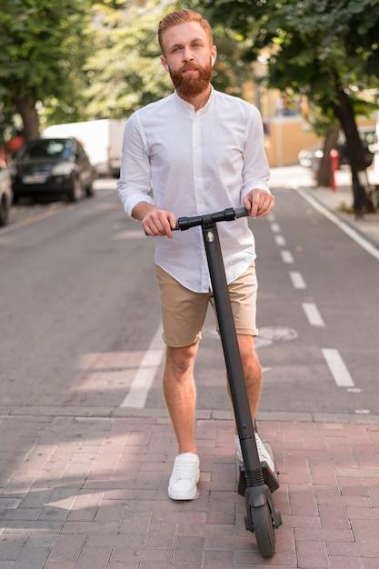 Vista frontale barbuto uomo moderno su scooter Foto Gratuite