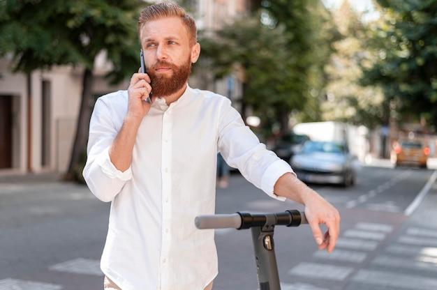 Vista frontale barbuto uomo moderno parlando al telefono su scooter Foto Gratuite