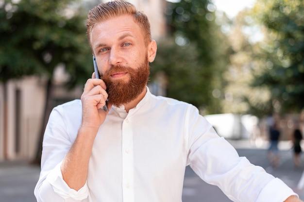 Vista frontale barbuto uomo moderno parlando al telefono Foto Gratuite