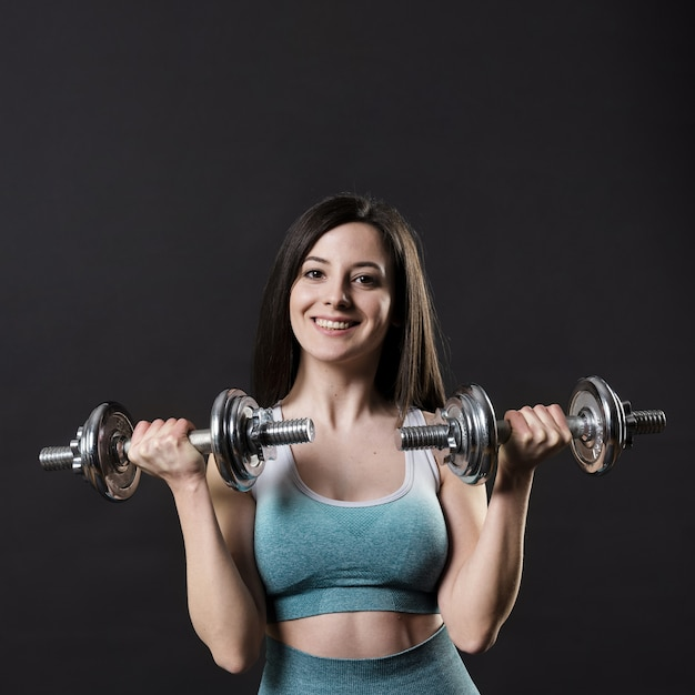 Front view of beautiful woman with dumbbells Free Photo