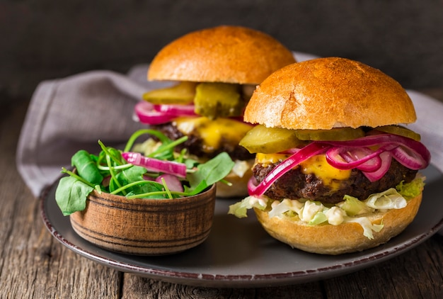 Front view beef burgers with pickles on cutting board Free Photo