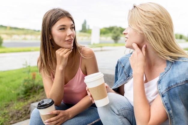 Migliori amici di vista frontale che tengono alcuni bicchieri di carta di caffè Foto Gratuite