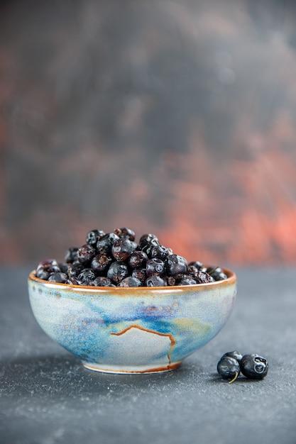Ribes nero di vista frontale nella ciotola sulla superficie isolata Foto Gratuite